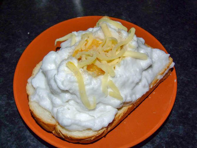 4. เอามาวางบนขนมปัง เจาะตรงกลางให้เป็นบ่อ เอาไข่แดงมาแทใส่ เอาเนยใส่บนไข่แดงนิดนึง โรยเกลือนิดหน่อย เอาชีสโรย พริกไทยตามชอบ